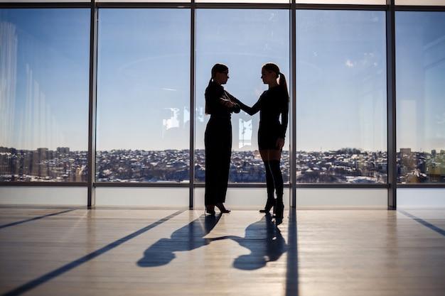 Dos mujeres de negocios disfrutando de la vista de la ciudad y hablando mientras están de pie junto a la ventana grande en la oficina