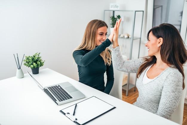 Dos mujeres de negocios jovenes que dan alto-cinco en oficina moderna. celebrando el éxito.