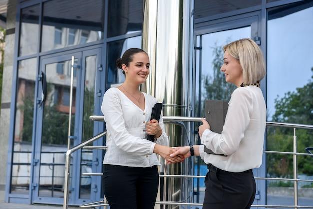 Dos mujeres de negocios en trajes apretón de manos antes del edificio de oficinas