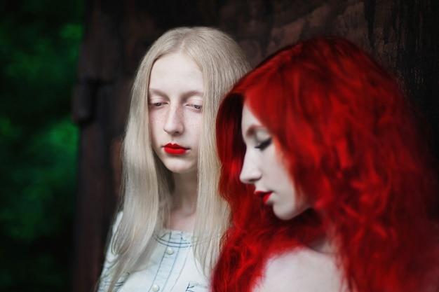 Dos mujeres, una niña con el pelo rojo rizado y una mujer con el pelo largo y liso y blanco