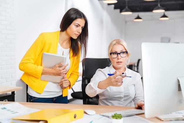 Dos mujeres de la oficina bastante jóvenes y maduras que tienen una reunión de lluvia de ideas en la mesa de la oficina