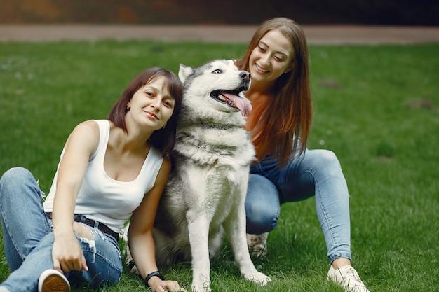 Dos mujeres en un parque de primavera jugando con lindo perro