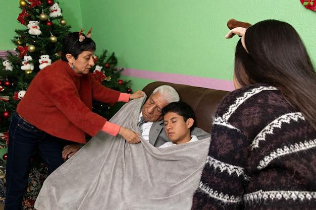 Dos mujeres que cubren con una manta dos hombres durmiendo en un sofá en navidad