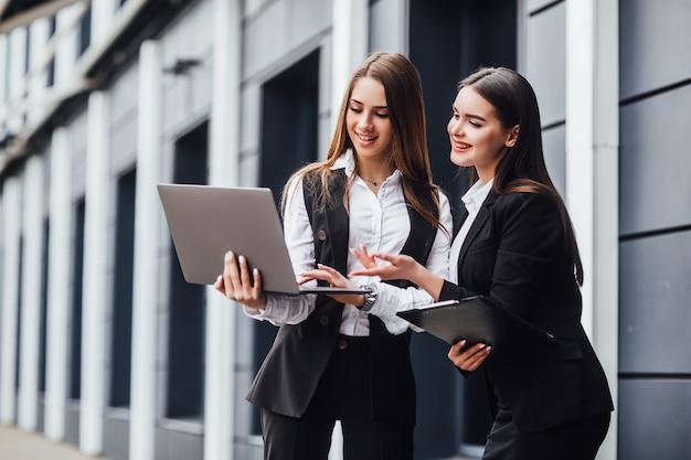 Dos mujeres que trabajan juntas en una computadora portátil con la presentación.