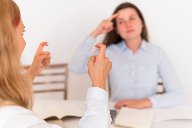 Dos mujeres que usan lenguaje de señas para conversar.