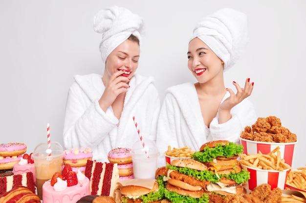 Dos mujeres de raza mixta felices se divierten después de tomar la ducha uno al lado del otro
