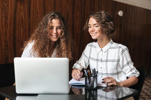 Dos mujeres rizadas felices trabajando junto a la mesa