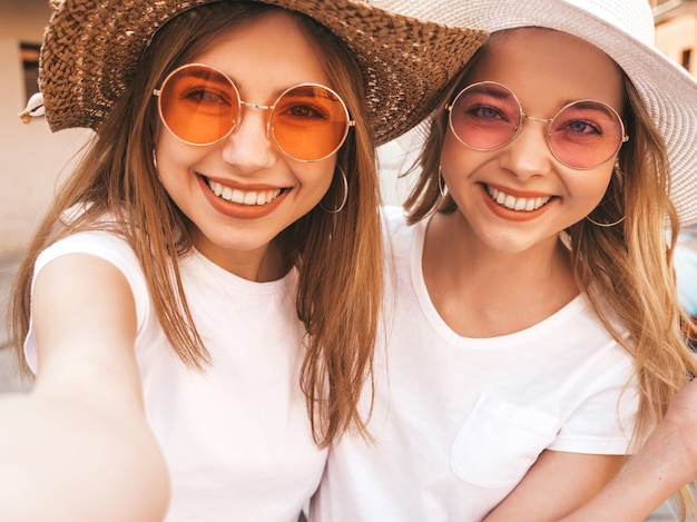 Dos mujeres rubias sonrientes jovenes del inconformista en ropa blanca de la camiseta del verano. chicas tomando fotos de autorretrato autofoto en el teléfono inteligente. .