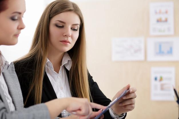 Dos mujeres sentadas en la oficina y mirando gráficos y tablas discutiendo algunas preguntas