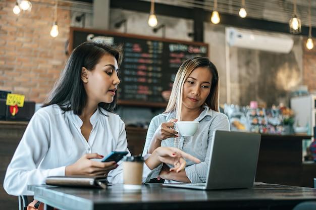 Dos mujeres sentadas y trabajando con una computadora portátil en una cafetería.