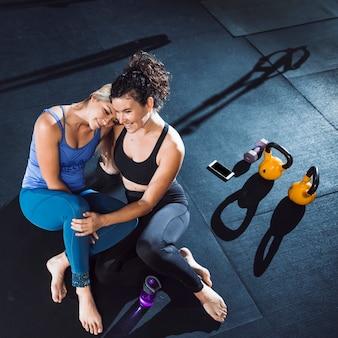 Dos mujeres sonrientes atléticas sentados juntos en el gimnasio