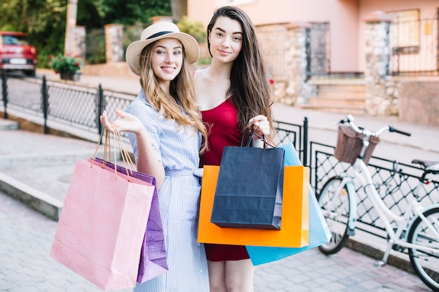 Dos mujeres sonrientes con bolsas de papel
