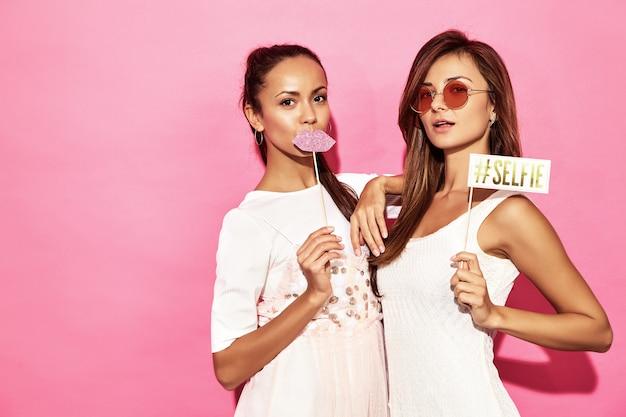 Dos mujeres sonrientes divertidas con labios grandes y selfie en palo. concepto inteligente y de belleza. alegres modelos jóvenes sexy listos para la fiesta. mujeres calientes aisladas en pared rosa. hembra positiva