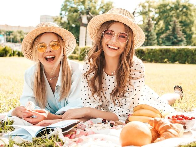 Dos mujeres sonrientes hermosas jóvenes en vestido de verano de moda y sombreros. mujeres despreocupadas haciendo picnic al aire libre.