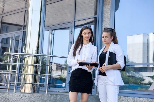 Dos mujeres sonrientes mirando tableta fuera del edificio de oficinas