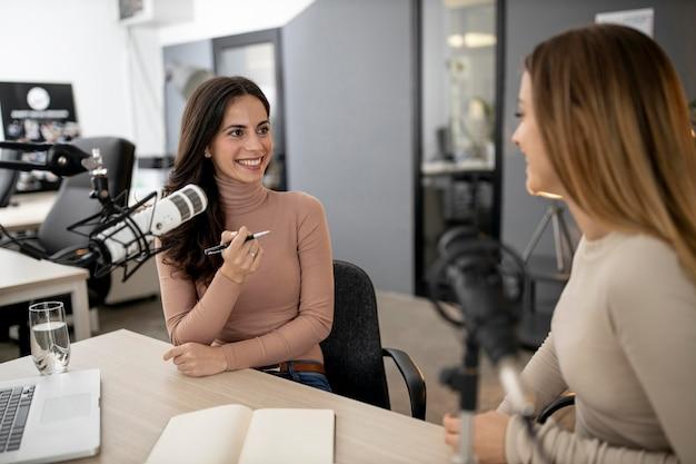 Dos mujeres sonrientes transmitiendo por radio juntos
