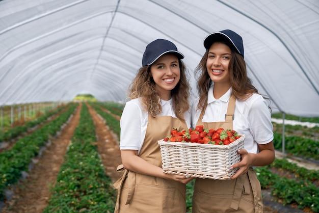 Dos mujeres sostienen una canasta de fresas