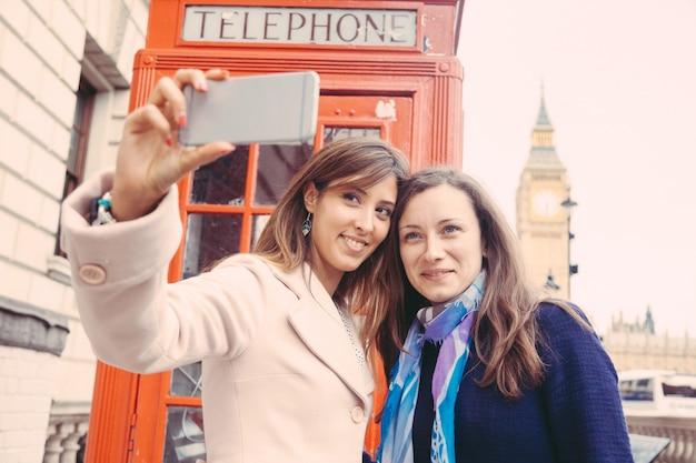 Dos mujeres tomando un selfie en londres.