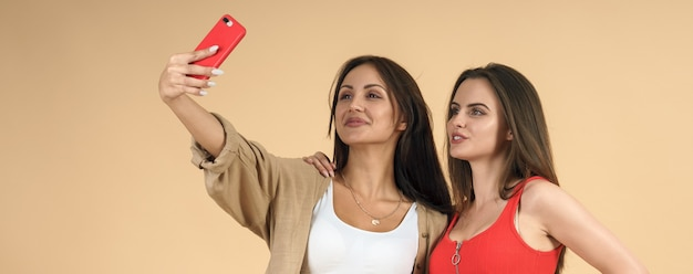 Dos mujeres tomando selfie móvil en pared beige