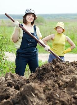 Dos mujeres trabajan con estiércol