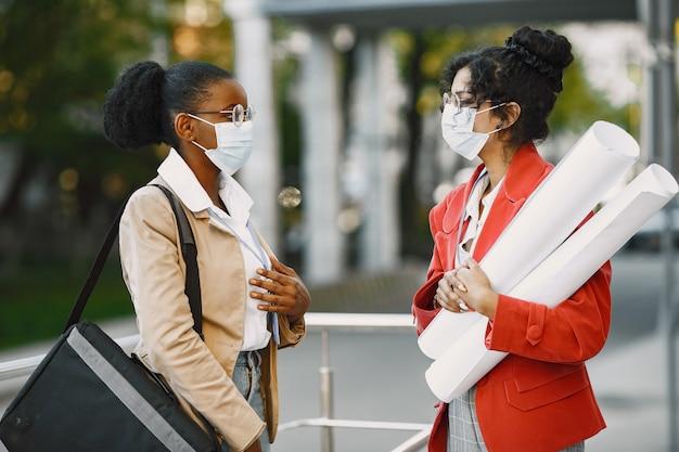 Dos mujeres trabajando como arquitectas en una restricción. personas que toman una decisión sobre el plan de un edificio. concepto de cuarentena