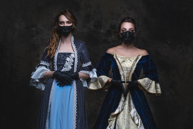 Dos mujeres en traje renacentista, mascarilla y guantes, concepto antiguo y nuevo