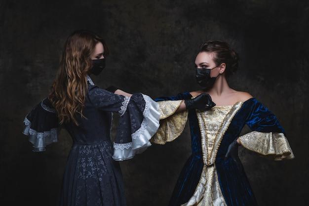 Dos mujeres en traje renacentista, mascarilla y guantes saludando chocando los codos, concepto antiguo y nuevo