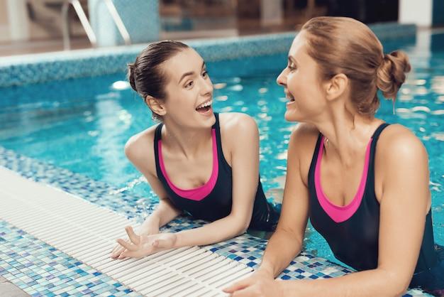 Dos mujeres en trajes de baño en el borde de la piscina en el gimnasio.