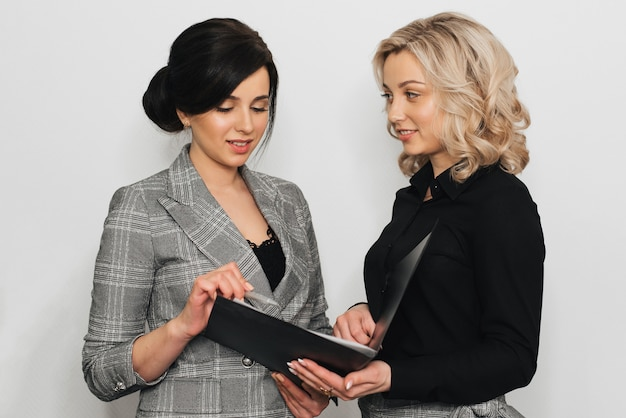 Dos mujeres en trajes de negocios secretarias rubias y morenas