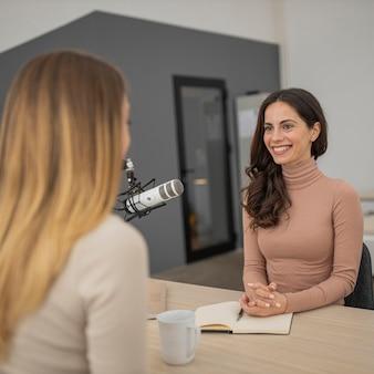 Dos mujeres transmitiendo juntas en la radio.
