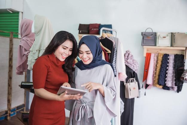Dos mujeres usando tableta en tienda de moda