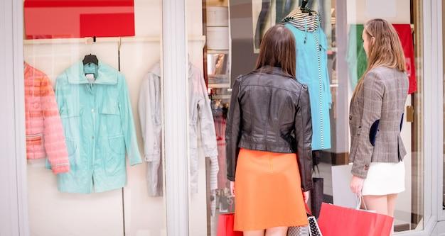 Dos mujeres de la ventana trasera de compras en el centro comercial
