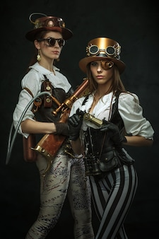 Dos mujeres vestidas al estilo de steampunk con brazos