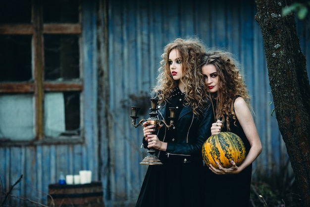Dos mujeres vintage como brujas, posando frente a una casa abandonada en la víspera de halloween