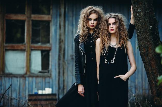 Dos mujeres vintage como brujas, posando junto a un edificio abandonado en vísperas de halloween