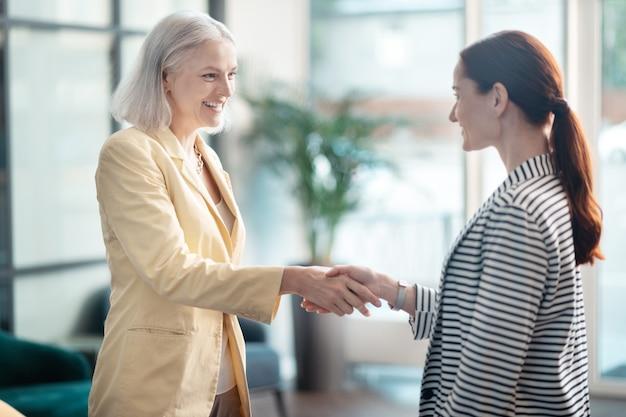 Dos mujeres. vista lateral de dos empresarias sonrientes estrecharme la mano en su reunión de negocios en el edificio de oficinas
