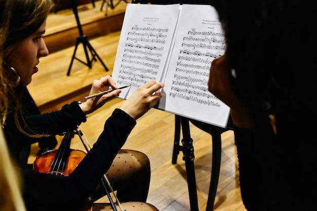 Dos músicas que corrigen una partitura con un lápiz antes de que la orquesta comience a tocar.