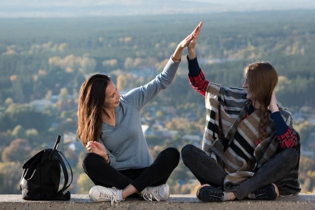 Dos niña feliz sentado en el fondo de la naturaleza. amistad. cinco altos. vista frontal