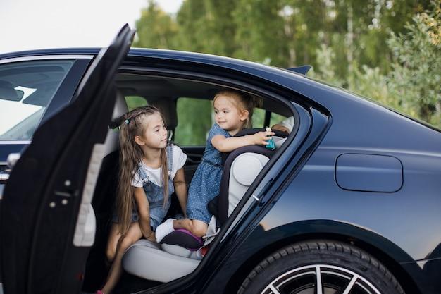 Dos niñas en el asiento trasero de un coche.