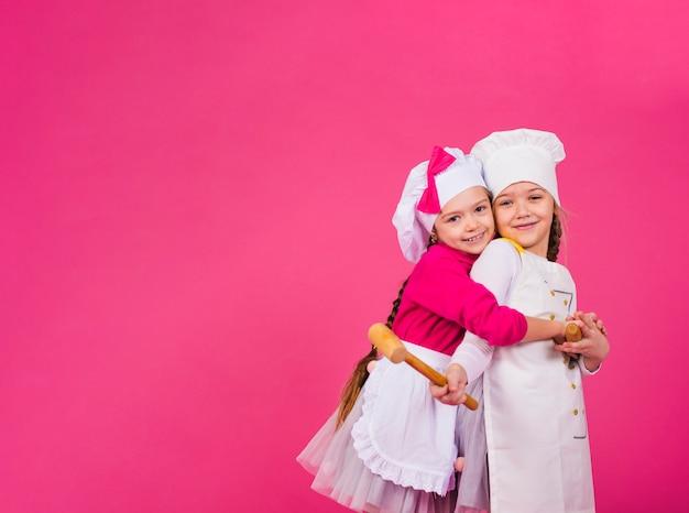 Dos niñas cocinan con utensilios de cocina abrazándose.