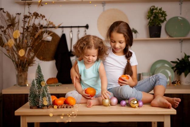 Dos niñas comiendo mandarinas en la cocina de navidad