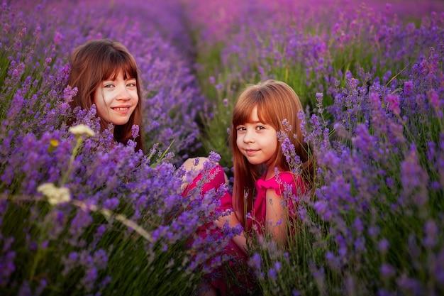 Dos niñas divertidas juegan en un campo de lavanda