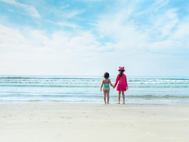 Dos niñas están de pie y mano a mano en la playa y el mar.