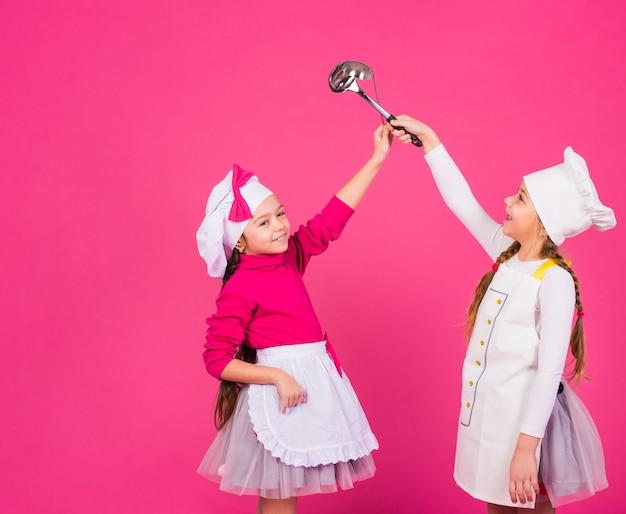 Dos niñas felices cocineros de pie con cucharones