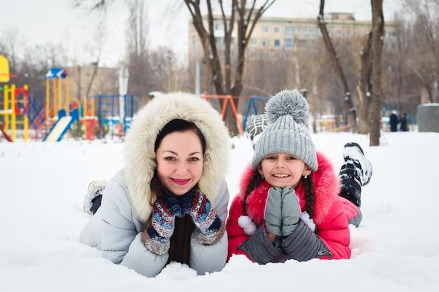 Dos niñas felices, madre e hija jugando en un parque infantil en el parque de la ciudad.