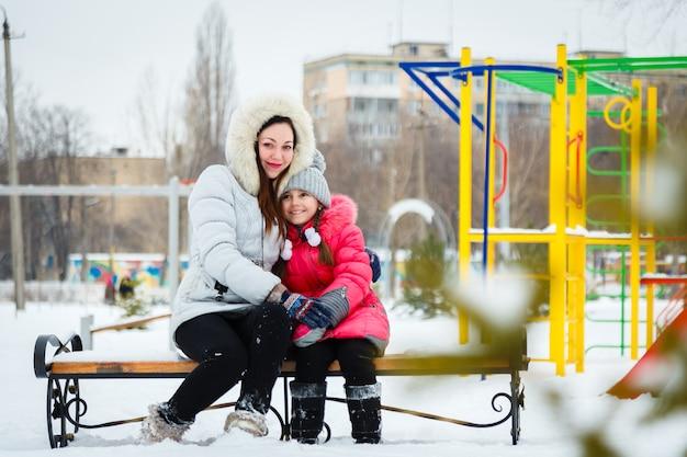 Dos niñas felices, madre e hija sentada en un banco en un patio de recreo en el parque de la ciudad.