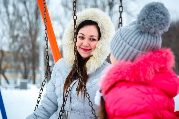 Dos niñas felices, madre e hija sentada en un columpio en un parque infantil en el parque de la ciudad.