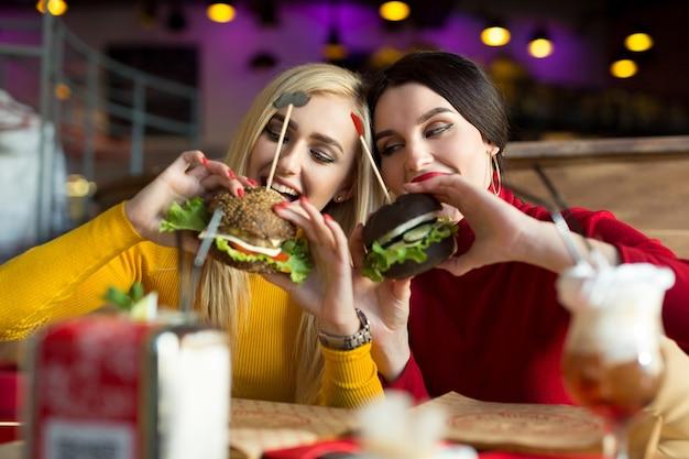 Dos niñas felices muerden hamburguesas. concepto de comida rápida