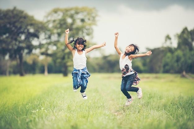 Dos niñas felices saltan en el parque natural