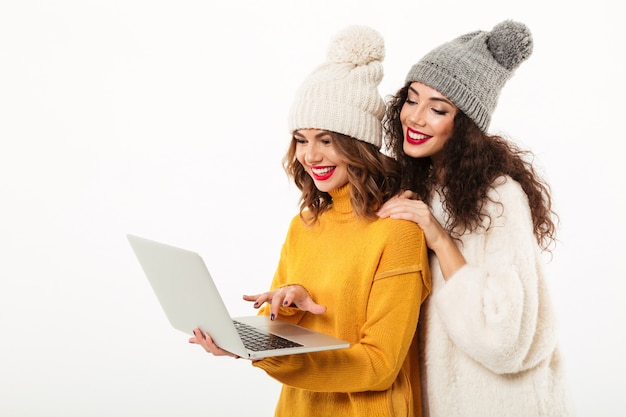 Dos niñas felices en suéteres y sombreros parados juntos mientras usa la computadora portátil sobre la pared blanca